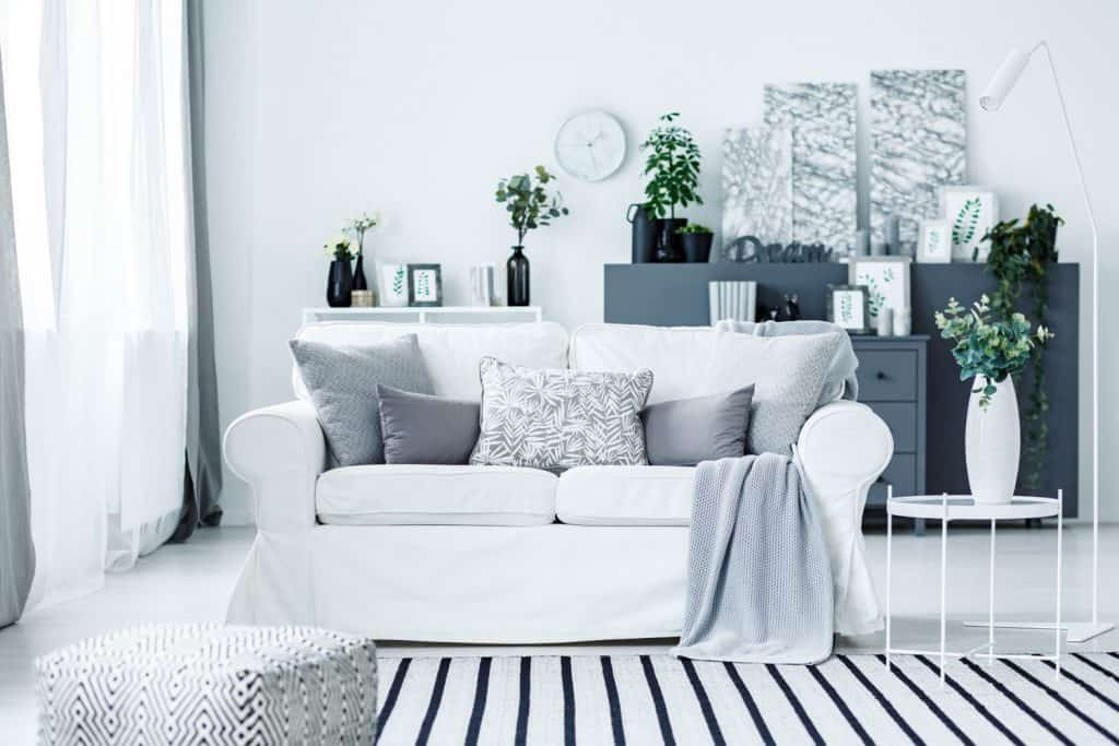 A white and light blue themed living room with a white loveseat sofa, light gray ottoman, and a white metal framed end table