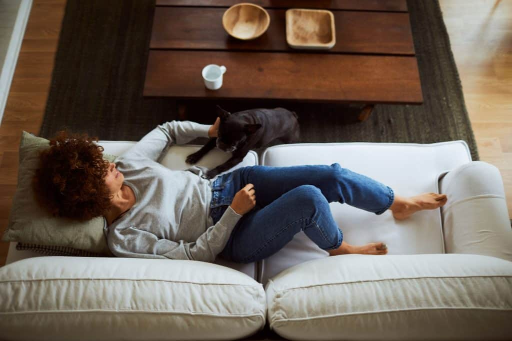 A woman lying on a loveseat sofa with her dog on the side