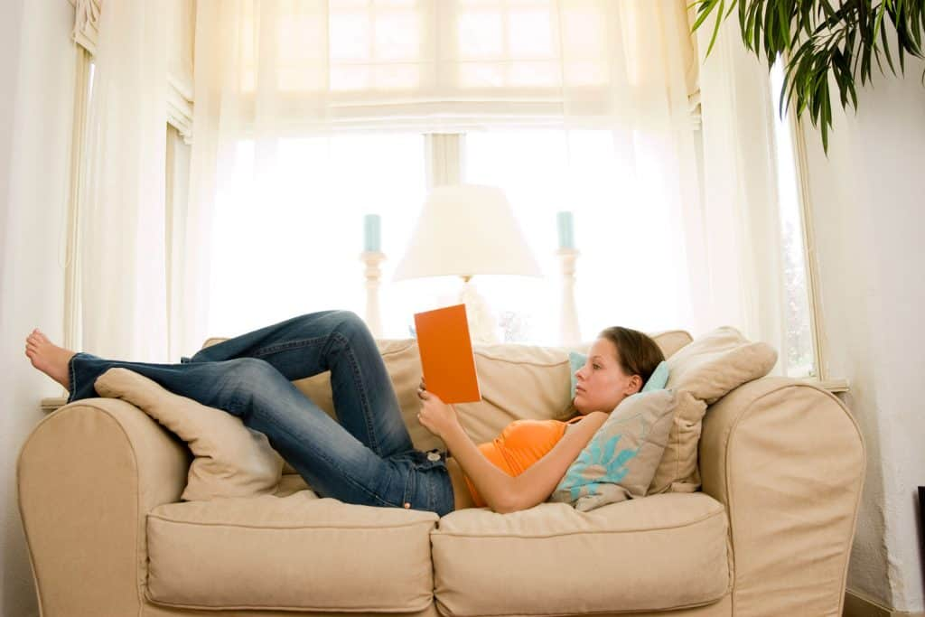 A woman lying on her loveseat sofa while reading a book