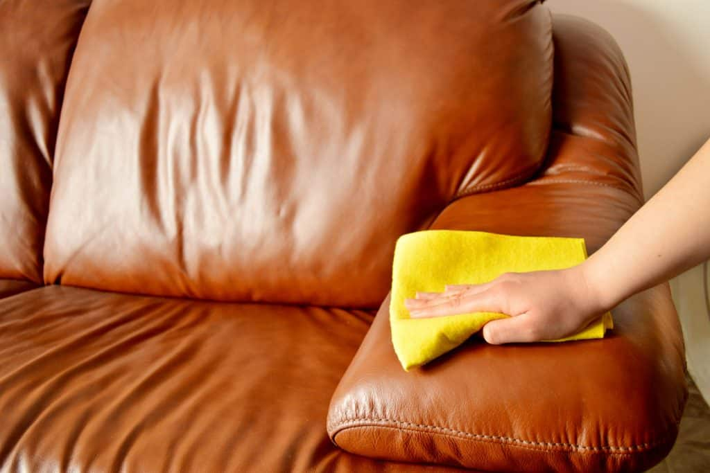A woman wiping the leather couch with a yellow cloth