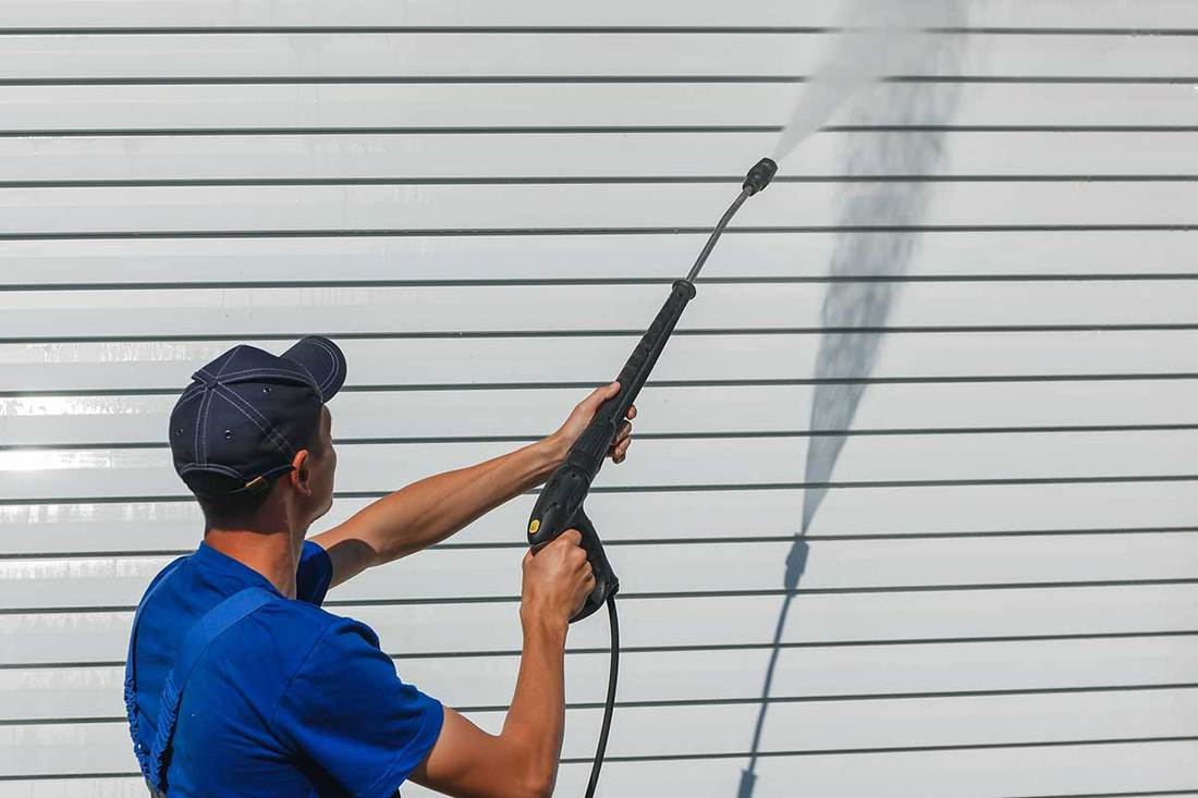 A worker in overalls washes a white wall from a siding with a water gun, How To Clean Vinyl Siding Without Killing Plants