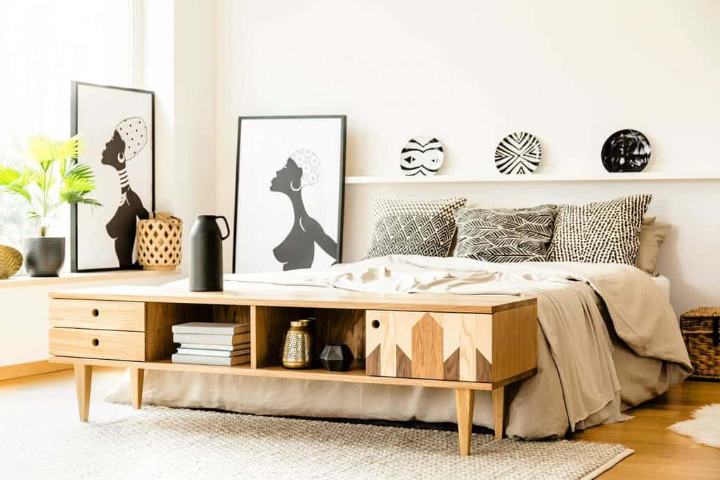 African posters next to bed with patterned cushions in bedroom interior with wooden cupboard