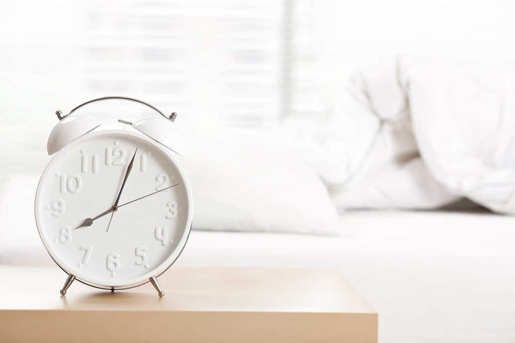 Alarm clock standing on night table at sleeping room