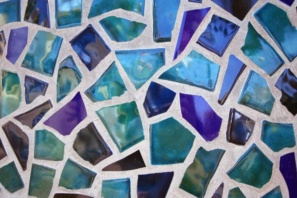 An abstract pattern masaic in broken tiles, in shades of blue and green