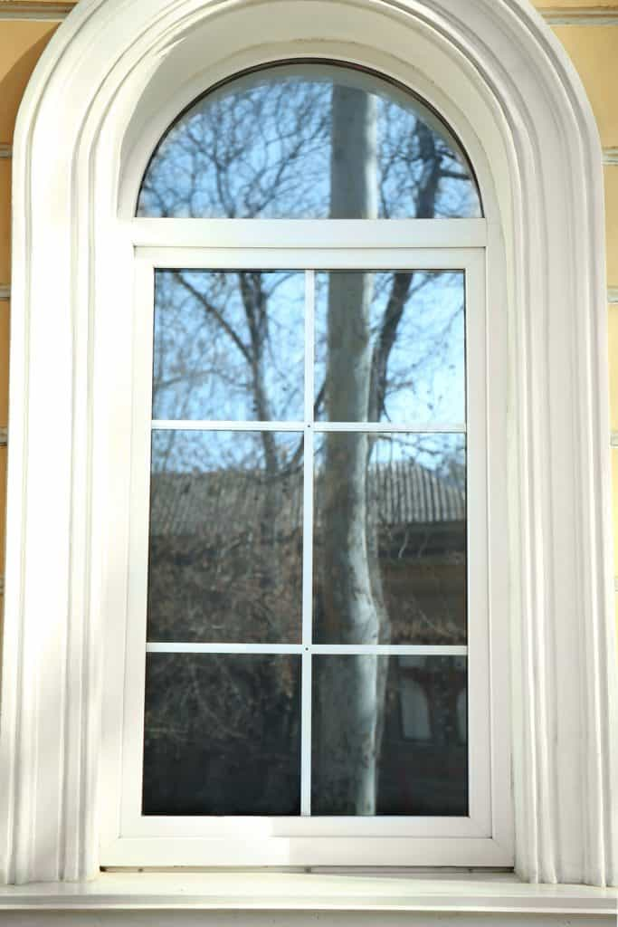 A narrow arched window with white painted concrete framing