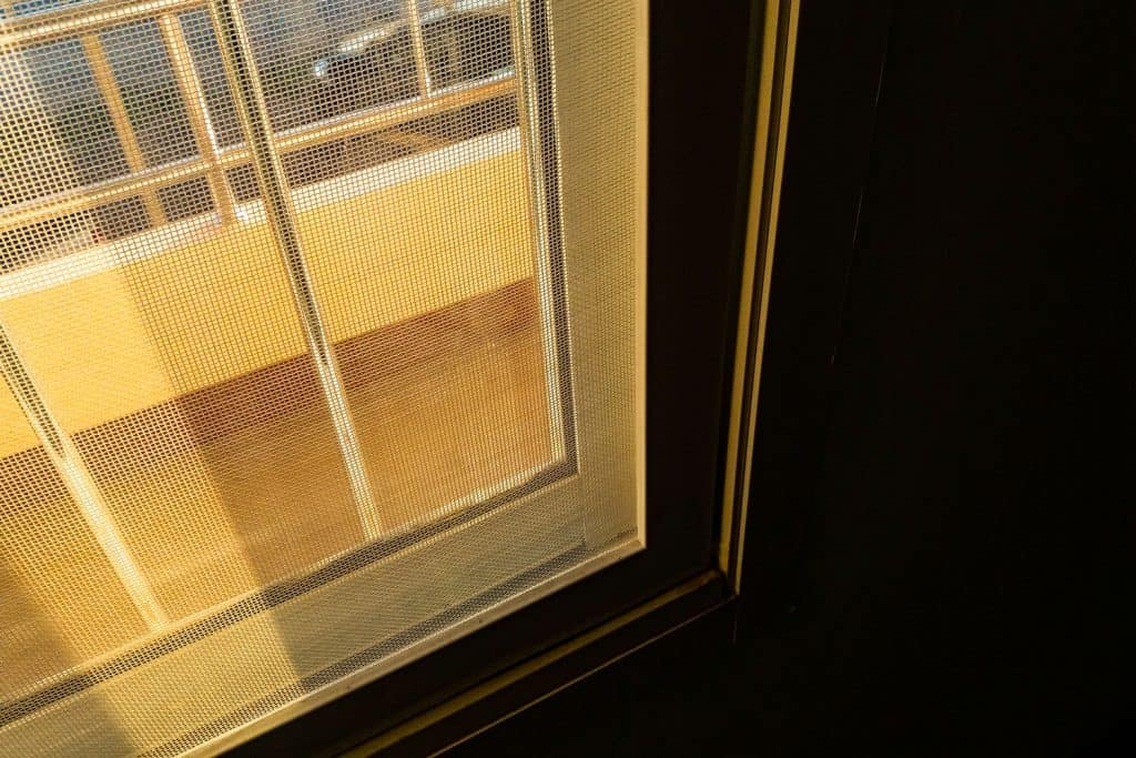 An up close photo of a screen door of a house