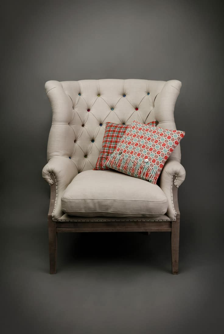 Wingback chair, Armchair and 2 colourful cushions on grey background