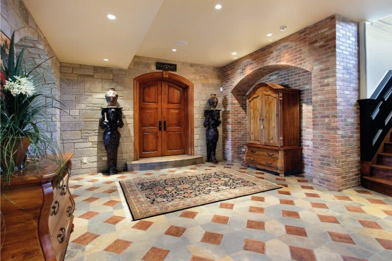 Basement foyer area vintage style with statues on the sides of a wooden door, How Big Should A Foyer Rug Be?