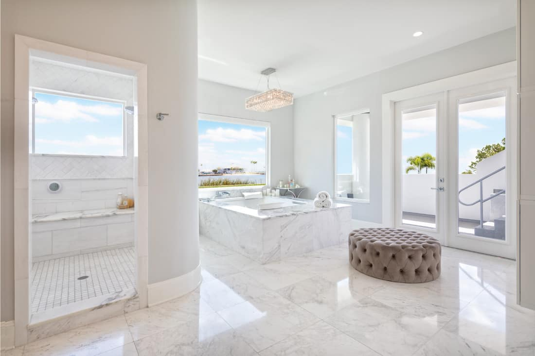 Beautiful master bathroom interior with free standing bath tub surround by natural stone marble