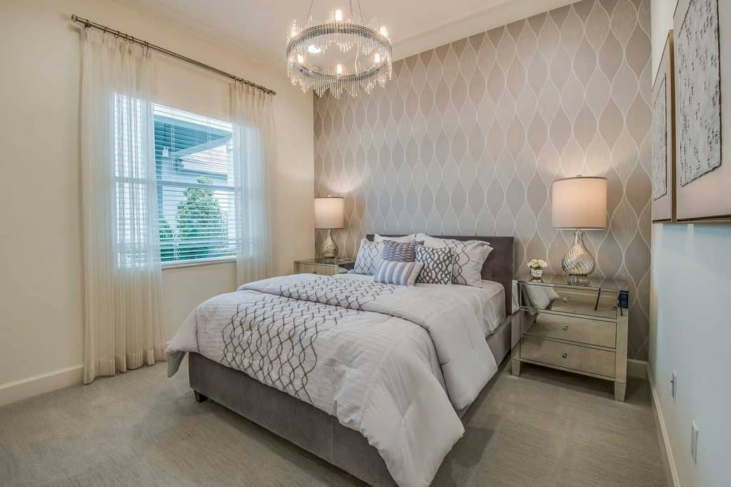 Beautiful bedroom with decorative wallpaper and sheer curtains