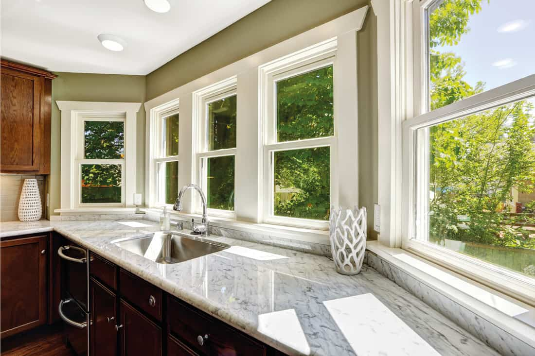 Beautiful kitchen cabinet with marble top, no window treatment and steel sink