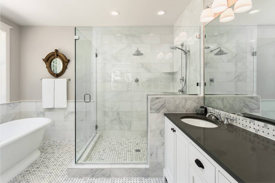 Beautiful master bathroom with shower, bathtub, and sink, with high end furnishings, lights on, with same color flooring and wall