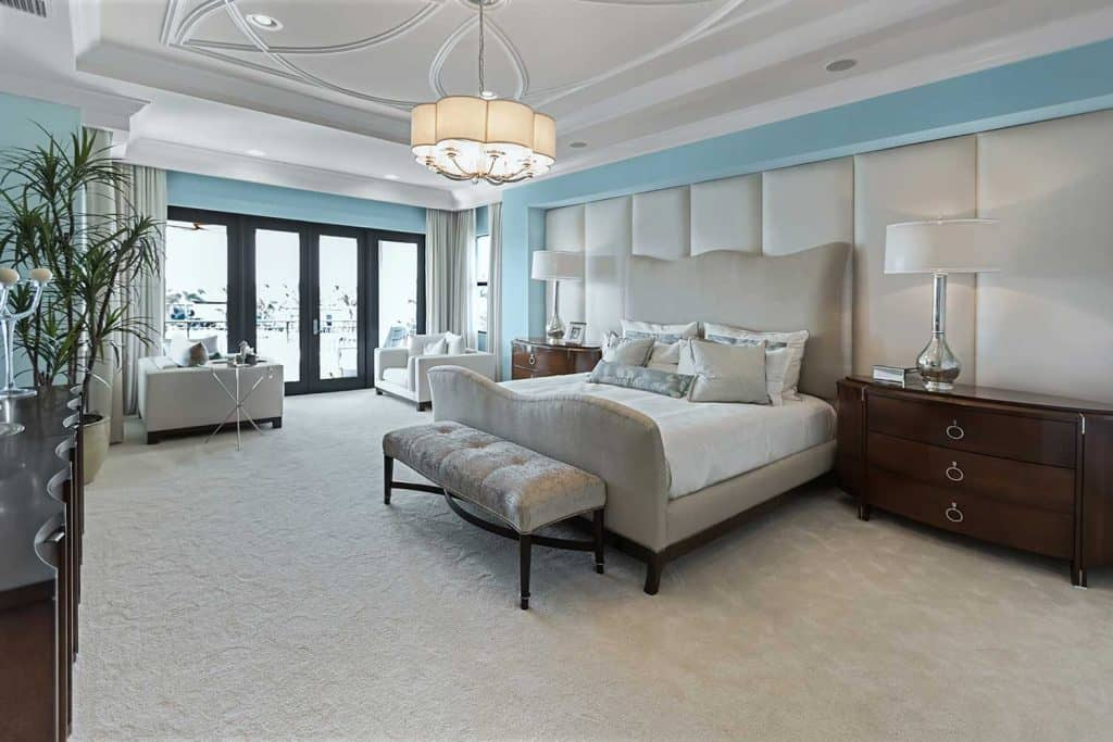 Beautiful master bedroom interior with carpet floor and french glass doors to balcony