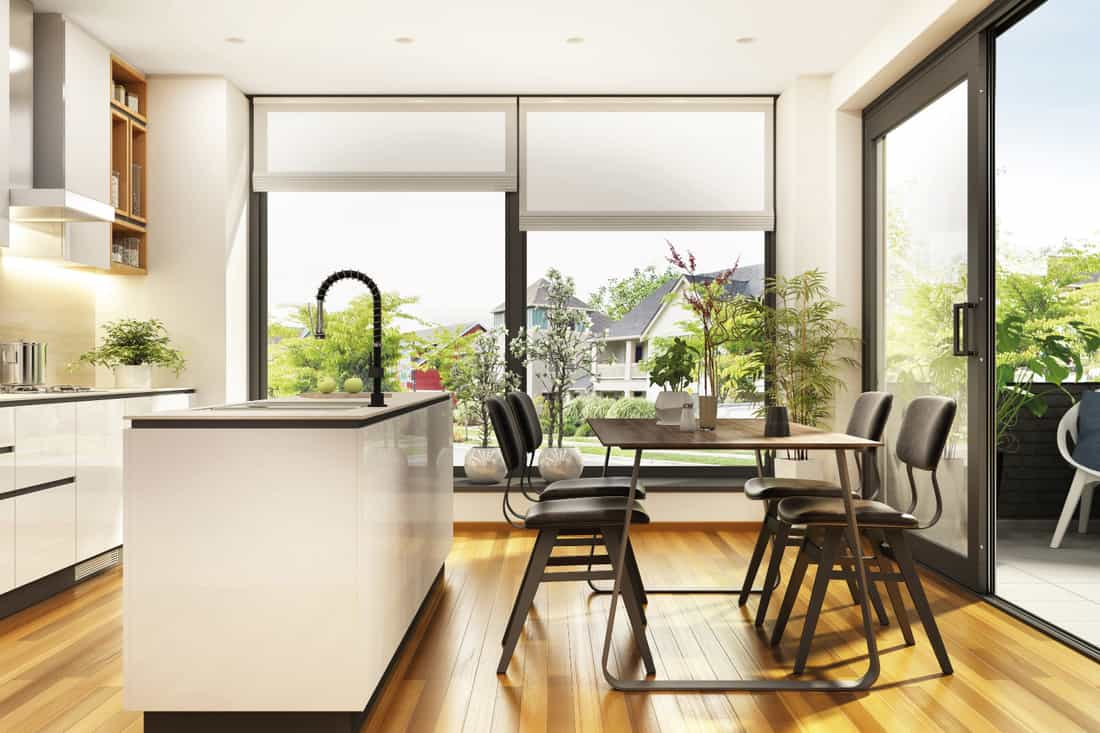 Beautiful white kitchen with large windows with roller shades and a terrace in the modern home