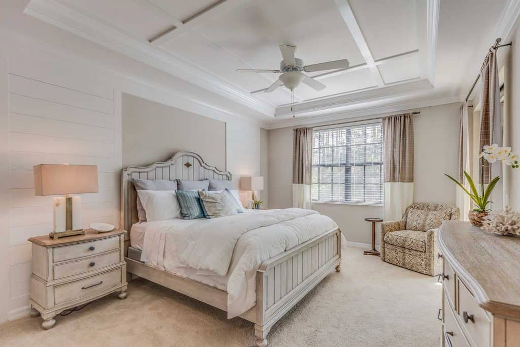 Beautifully decorated master bedroom with white and light brown tones, ceiling fan and coffered ceiling