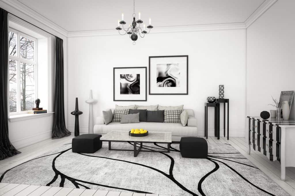 Black and white themed living room with a gray carpet, dark colored furnitures, and a gray sofa with a black curtain on the side