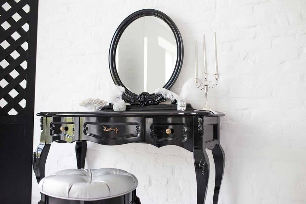 Black boudoir table in a bright room with a white brick wall