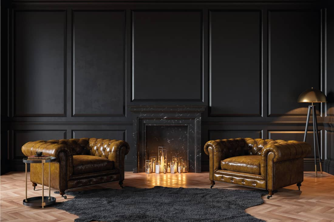 Black classic interior with fireplace, leather armchairs, carpet, candles