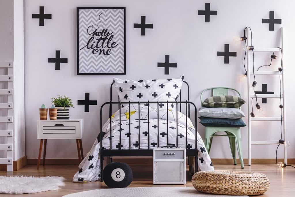 Black crosses on white wall and bedding in stylish bedroom interior with industrial metal bed and modern mint gray chair