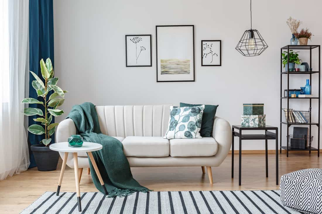 Black table next to sofa with green blanket in cozy apartment interior with gallery of posters