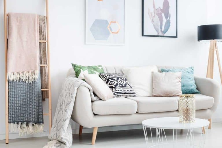 Blankets on ladder and white table on carpet in living room with lamp and cushions on sofa, How To Brighten A Living Room Without Windows