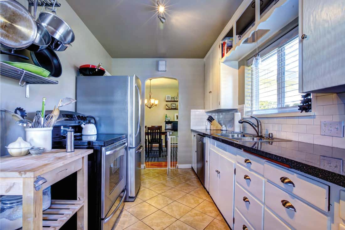 Blue kitchen interior with brown tile, stainless steel refrigerator and white cabinets, pots and pans are hung up on the sides
