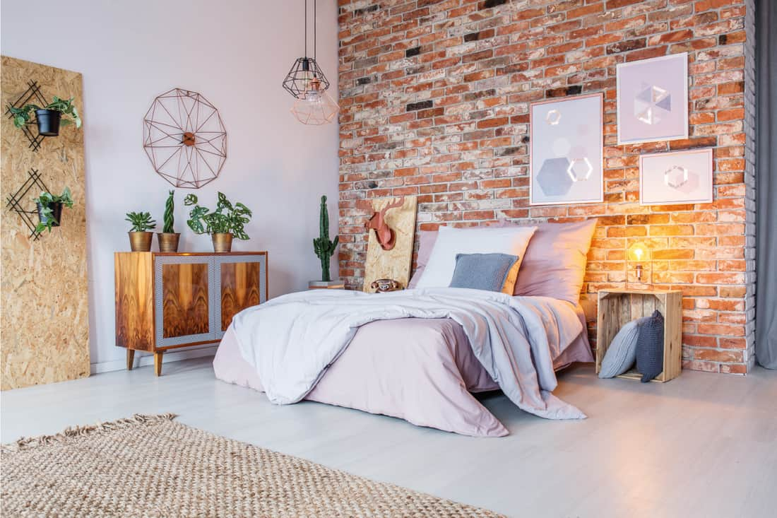 Bright bedroom with double bed, brick wall and rug, geometric bliss bedroom decor