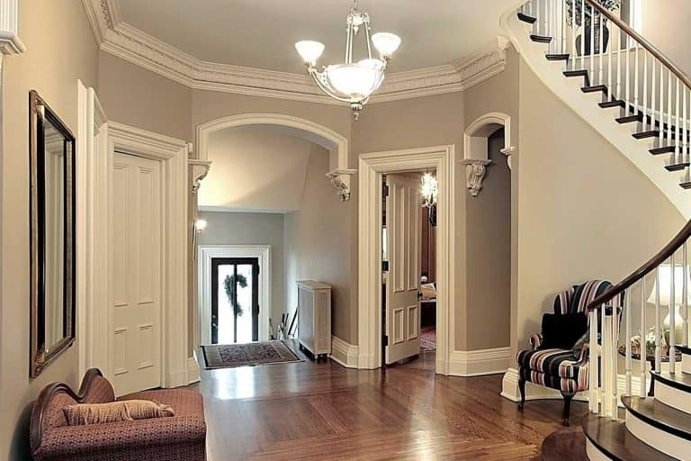 Bright foyer with chandelier and curved staircase, How Bright Should A Foyer Light Be?