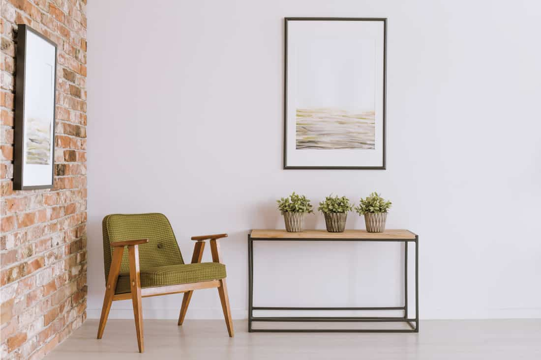 Bright painting above cabinet with plants in vintage living room with mid century modern armchair