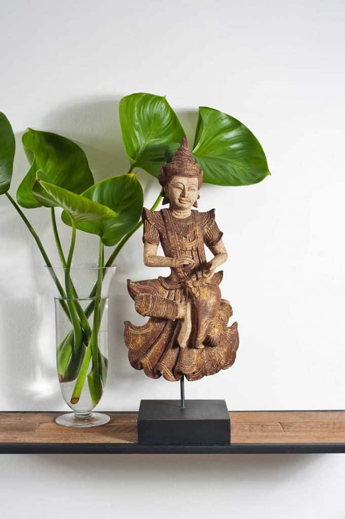 Buddha sculpture with green leaf decoration on side board