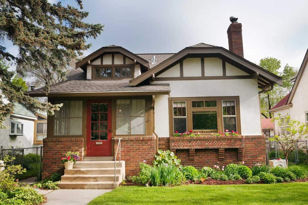 Bungalow house with stucco and brick walls, red front door, and window looking out to the lawn