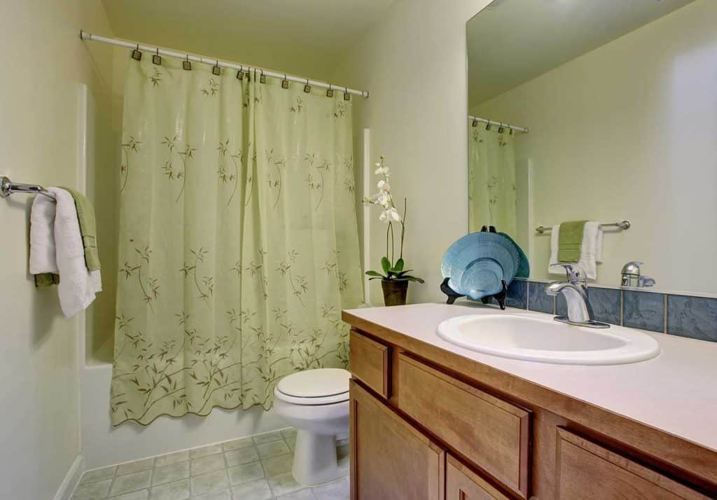 Classic bathroom with green shower curtain and tile floor