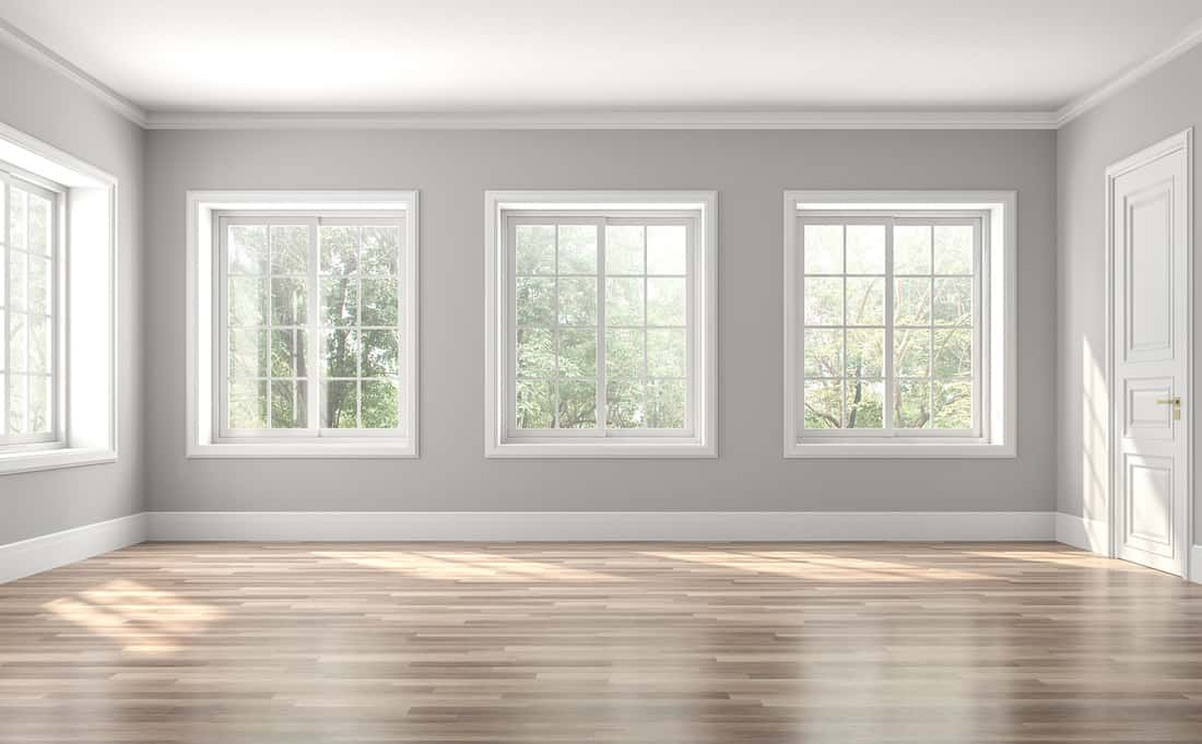 Classical empty room interior,The rooms have wooden floors and gray walls ,decorate with white moulding,there are white window looking out to the nature view.