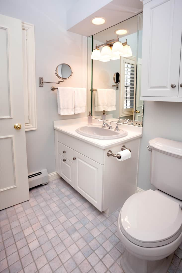 Clean, compact bathroom with small tiles as flooring