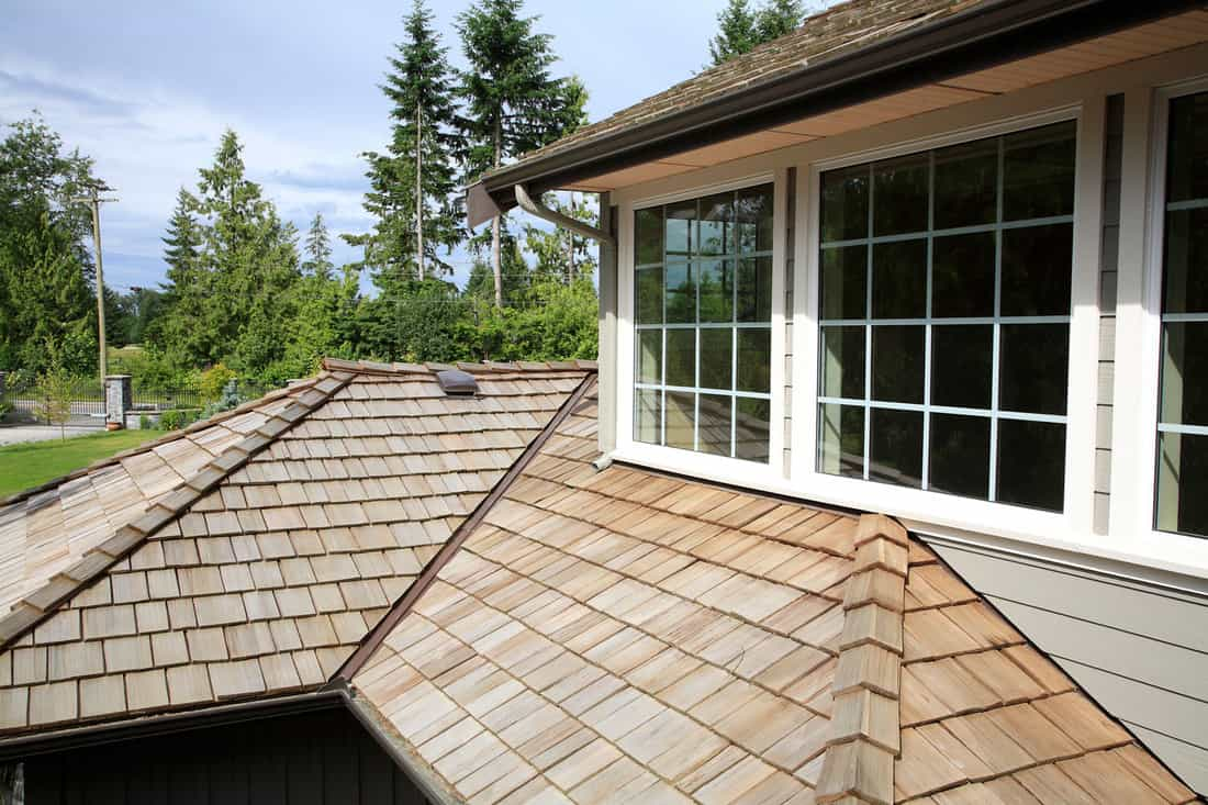 Close up looking down of New Cedar Shingle roof,gutters ,eaves and paned windows on a new home, Can Wood Shingles Be Painted?
