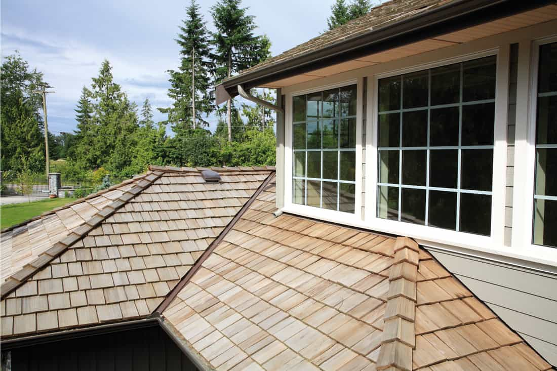 Close up looking down of new cedar shingle roof, gutters, eaves and paned windows on a new home