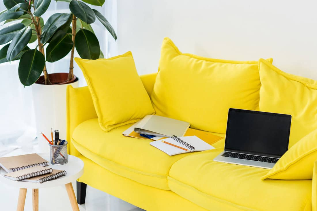 Close up view of laptop, notebooks and folders on yellow sofa at home office