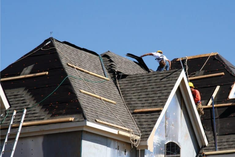 Construction workers putting shingles on the roof of a house, What Is The Best Wood For Roof Shingles?