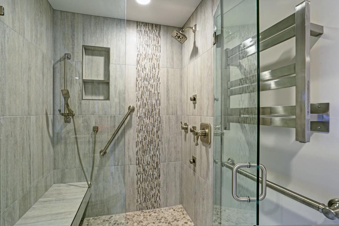 Contemporary bathroom design boasts gorgeous walk-in shower with tiled recessed shelves, built-in bench and accented with glass mosaic tiled vertical stripe, How to Add a Bench to an Existing Shower