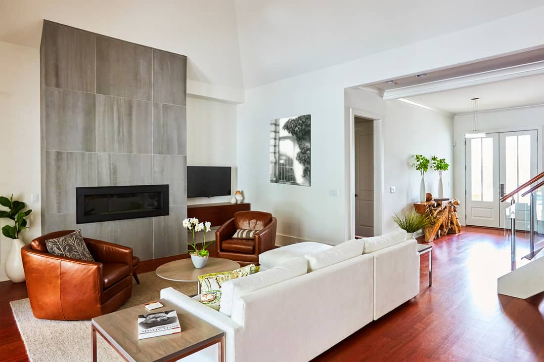 Contemporary fireplace with porcelain tile and leather furniture with contrasting color and fabric