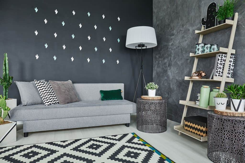 Contemporary inspired living room with a gray sofa, patterned rug and indoor plants all over the room