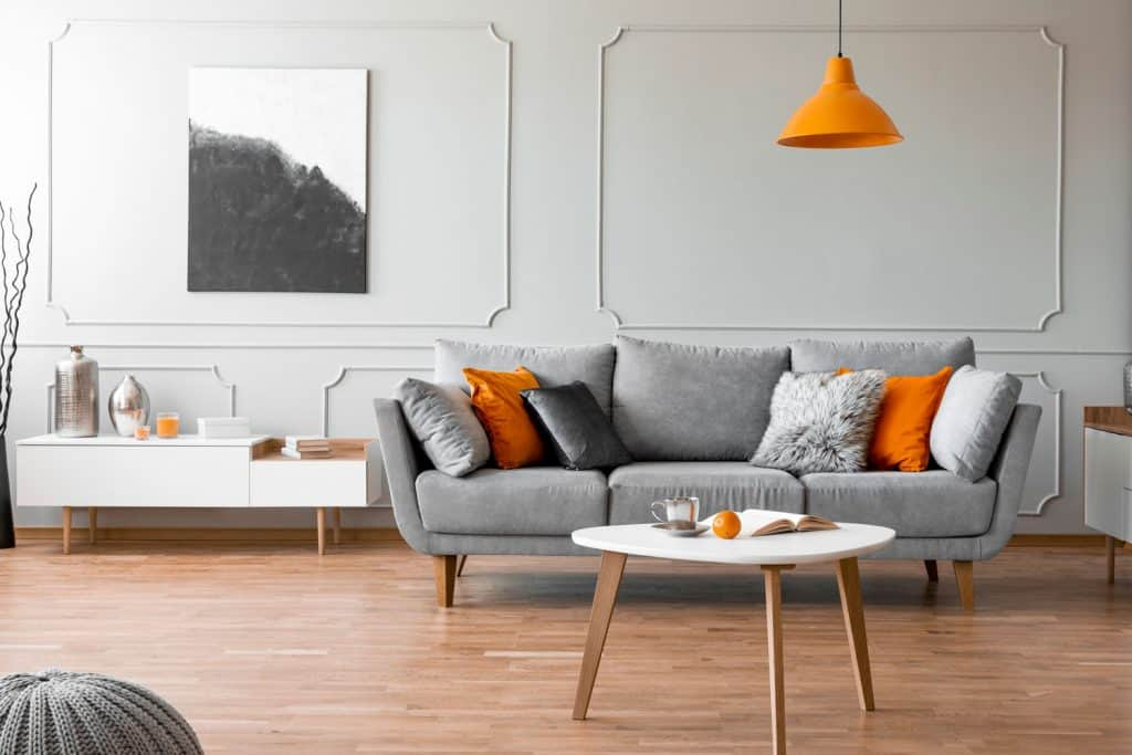 Contemporary living room interior with wooden laminated flooring, gray sofa with throw pillows, and a white end table