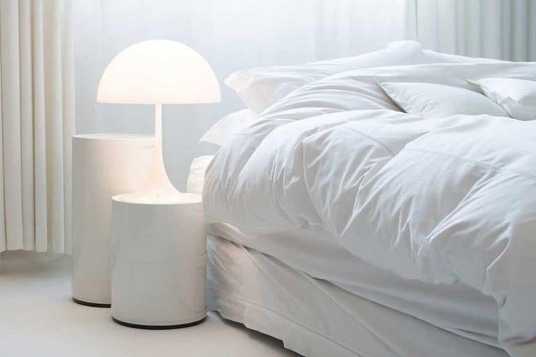 Cozy bed in a white bedroom interior with nightstand, 11 Great Bedroom Nightstands Ideas