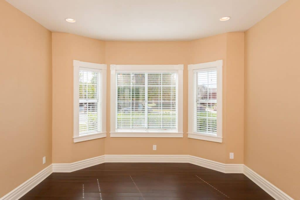 Cream painted walls and a bay window of a empty living room