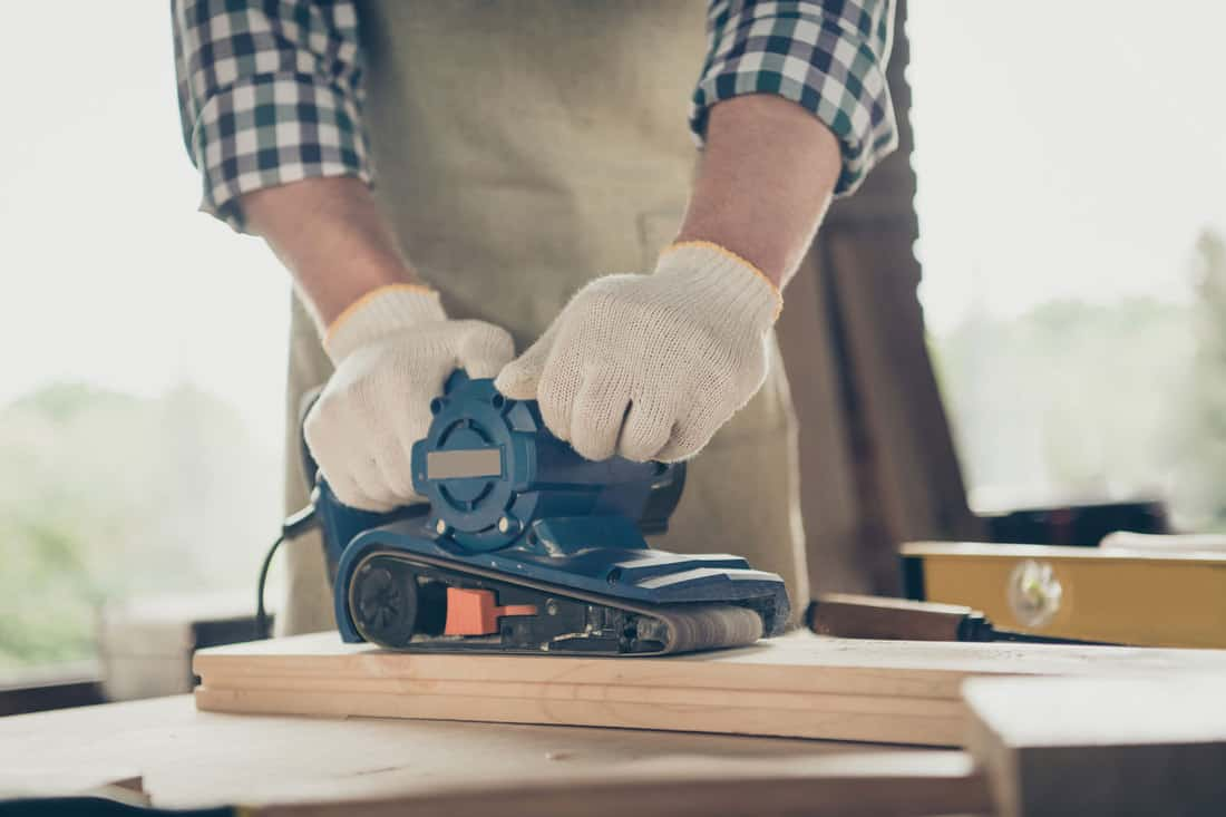 Cropped photo of foreman, guy making furniture using grinder and sandpaper in carpentry