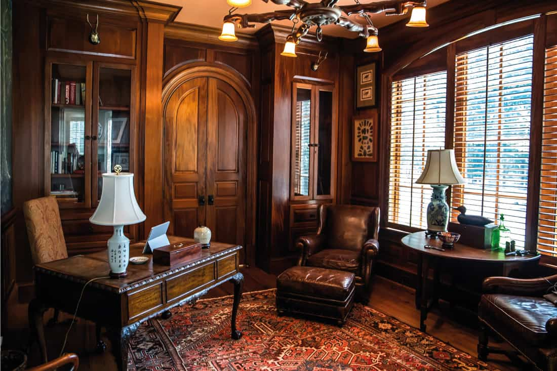 Dark stained wood stained home office with warm rust desert color with wood furniture, desk, lamp and oriental rug