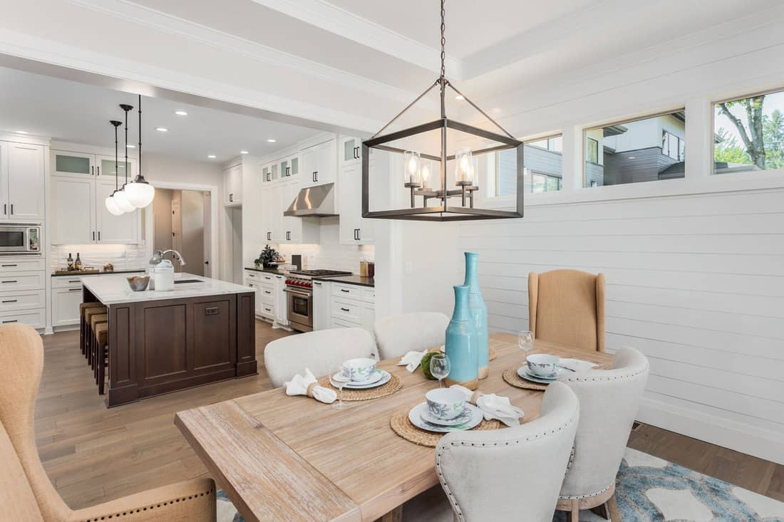 Dining Room and Kitchen Interior in New Luxury Home: Kitchen has Island, Sink, Cabinets, and Hardwood Floors. Dining Room has table with place settings,How To Mix And Match Dining Room Chairs