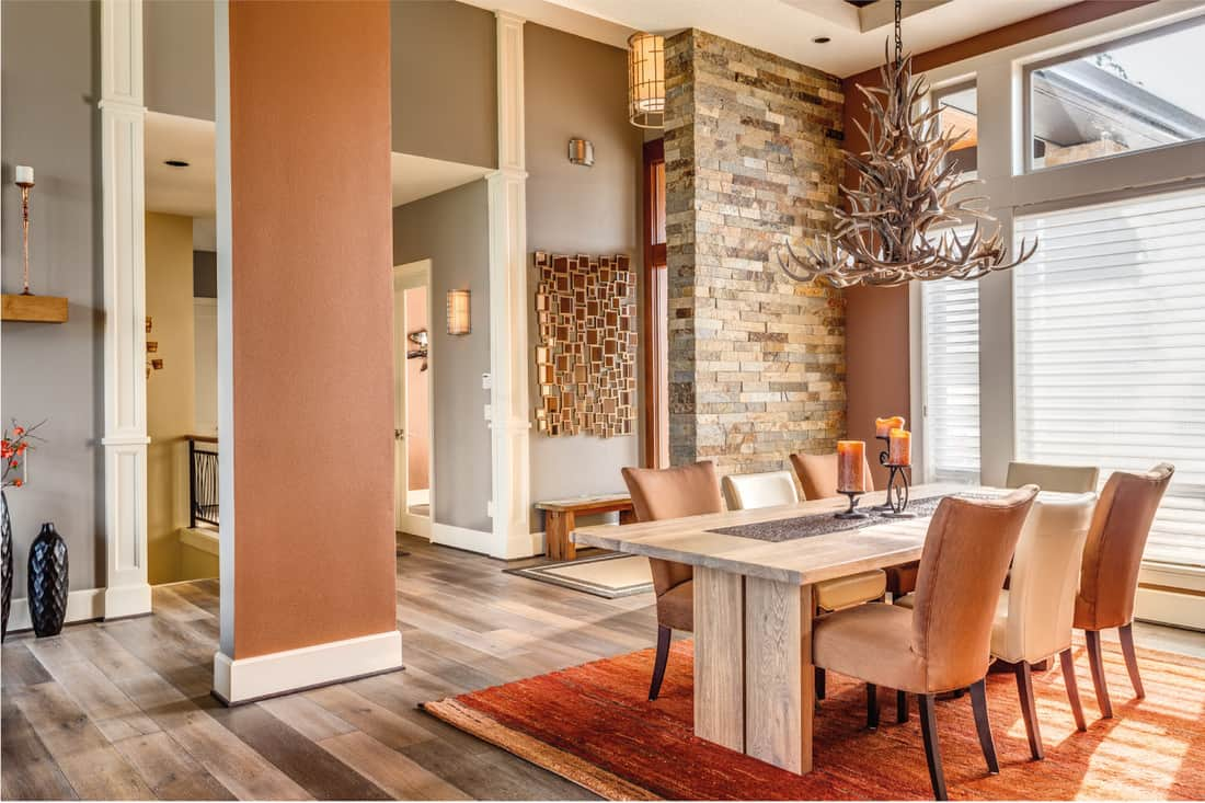 Dining room with entryway, table, elegant light fixture, and natural stone accent wall