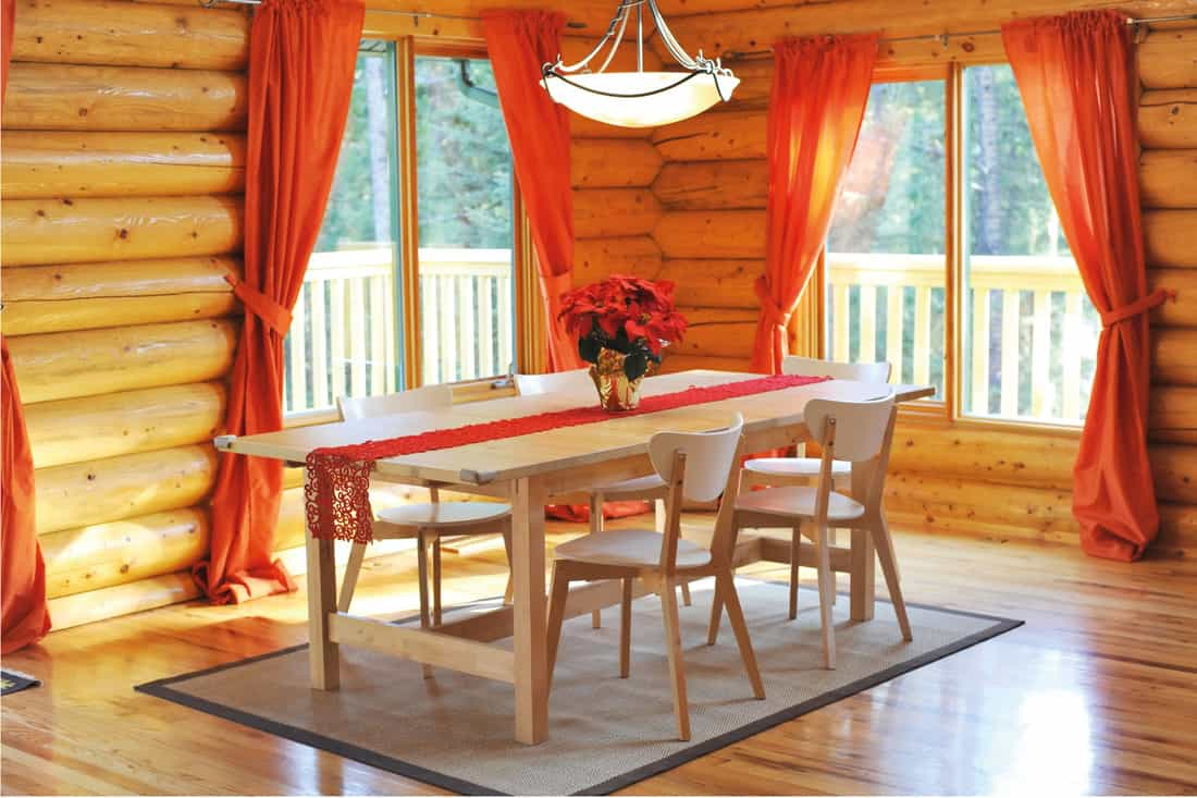 Dining room with hardwood floor in a rustic log house with red curtains