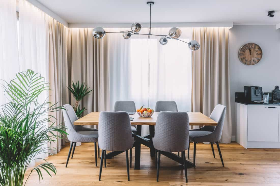 Dining room with wooden table and floor in modern apartment, blissful elegant layers